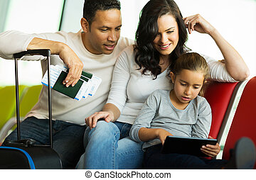family using tablet computer at airport - modern family...