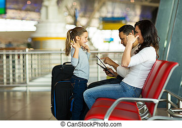 little girl playing a game with mother at airport