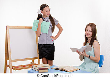 Teacher puts exellent student - Pupil stands at the...