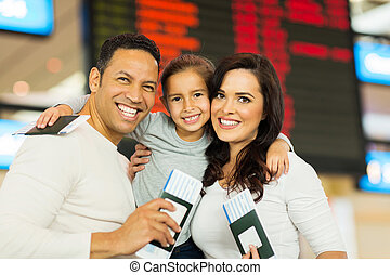family holding passports and boarding pass