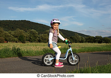 Happy four year old girl on a training bike