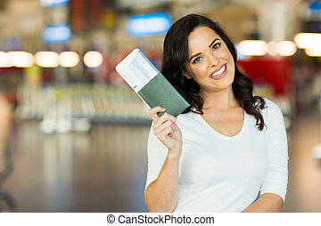 young woman holding passport and boarding pass - portrait of...
