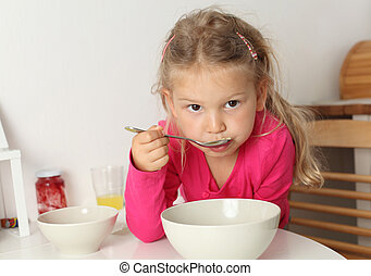 Cute four year old girl eats soup at home