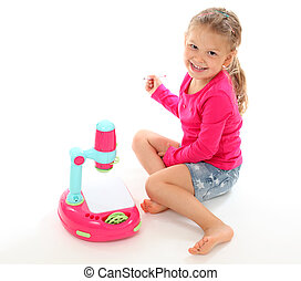 Little girl playing with a toy projector. Isolated over white background