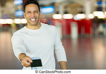 man handing over air ticket at check in counter