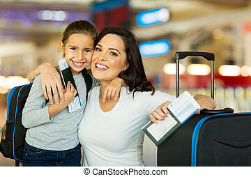 happy mother and daughter at airport travelling together