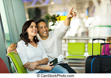 mid age couple at airport waiting for their flight - loving...
