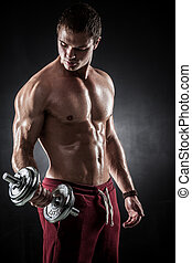 Fitness with dumbbells - Handsome athletic man pumping up...