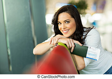 young woman relaxing at airport - happy young woman relaxing...
