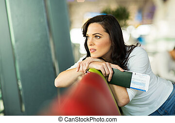 thoughtful woman sitting at airport looking outside