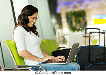 happy woman using laptop computer at airport
