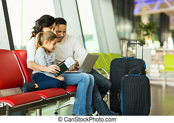 parents and daughter using laptop at airport - parents and...