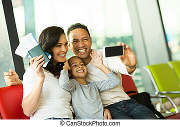 family taking self portrait with smart phone at airport -...
