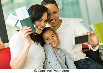 family taking selfie with smart phone at airport - beautiful...