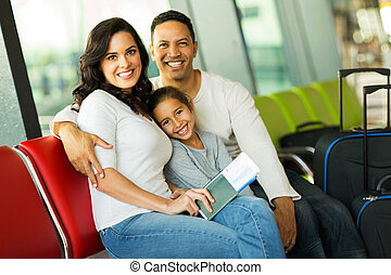 family of three at airport waiting for their flight -...