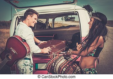 Multi-ethnic hippie couple with guitar packing luggage for a...