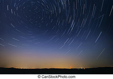 Startrail landscape of moving stars during the night of the...