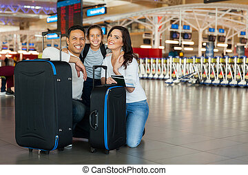 family with luggage bags at airport - cheerful family with...