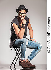 sexy smiling fashion man is sitting on a chair