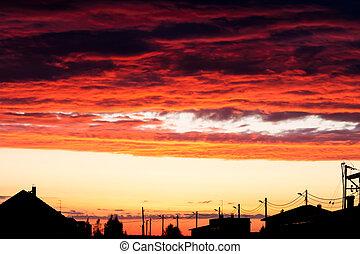 sunset lights up the clouds above an urban street