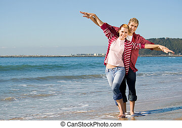 energetic couple - couple flying with their arms out wide