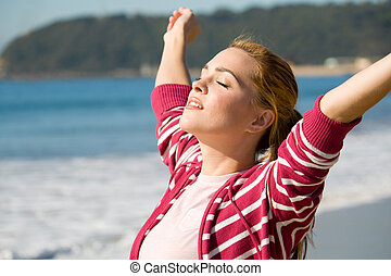 woman worshipping - woman with her arms out wide at beach