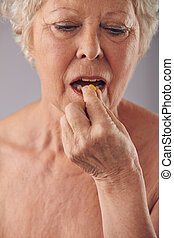 Senior woman taking a pill