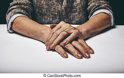 Senior womans hands clasped on a table - Close-up studio...