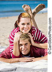 close couple - couple messing around on the beach blanket