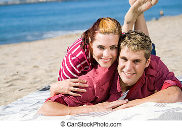happy couple - couple lying on beach together