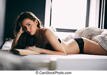 Young lady in lingerie on her bed with a book