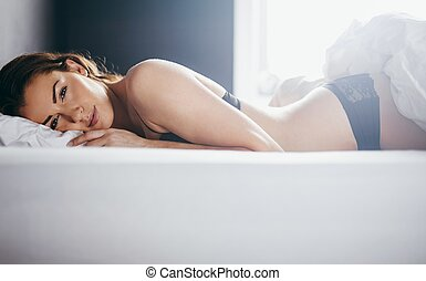 Woman in lingerie lying in her bed
