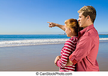 couple pointing out to sea