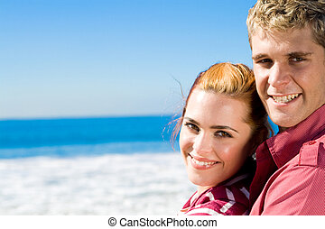 young couple - couple at the beach smiling