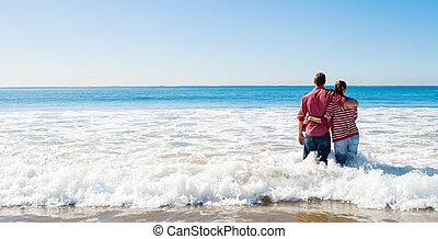 couple on beach - a couple in the distance standing knee...
