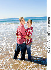 happy couple - a couple hugging in the seashore