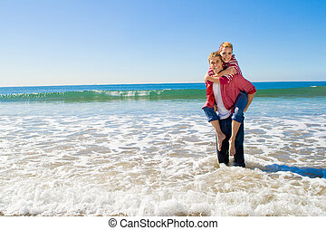 fun couple - a piggy-back ride in the shallow water