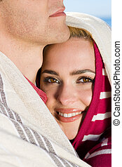 cosy couple - a woman holding her boyfriend with a hood on...