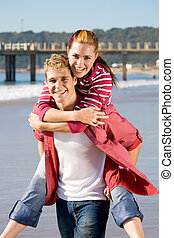 romantic piggy-back ride - a girlfriend riding on her...