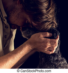 Loving man hugging his terrier dog - Retro image of loving...