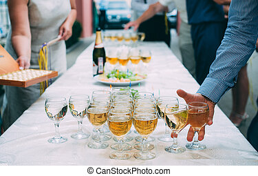 men's hand takes a glass of champagne at the wedding banquet