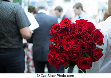 twenty-five red roses is a man in the crowd