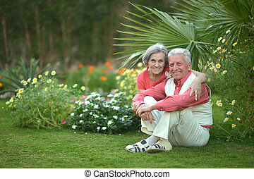Elderly couple sitting on grass at hotel resort