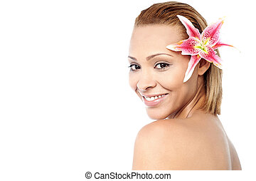 Smiling woman with pink lily flower