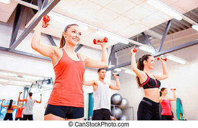 group of people working out with dumbbells - fitness, sport,...