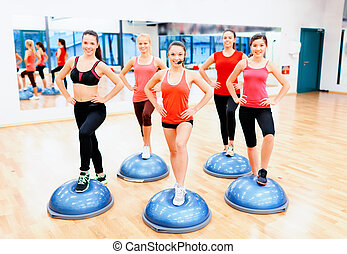 group of female doing aerobics with half ball - fitness,...