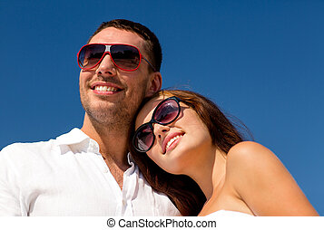 smiling couple over blue sky background