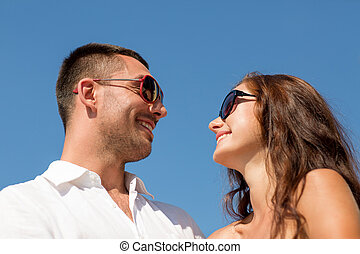 smiling couple over blue sky background - love, travel,...