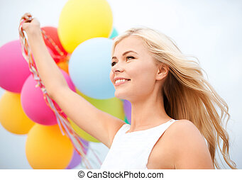 woman with colorful balloons outside - summer holidays,...