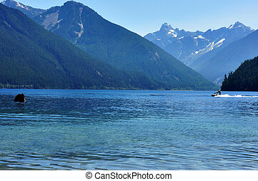 Chilliwack Lake with surrounding mountains and a seadoo on...